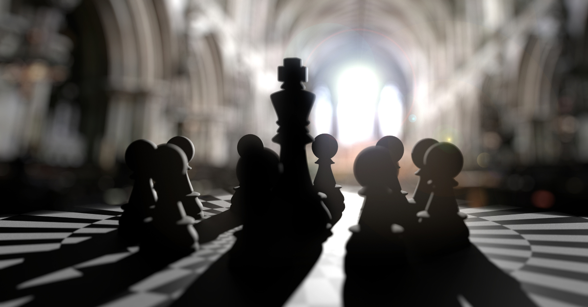 King chess piece in center of pawns leadership arrogance