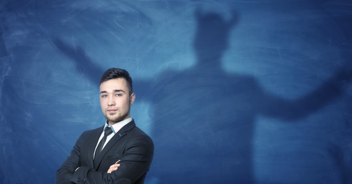 business man arms folded shadow is devil