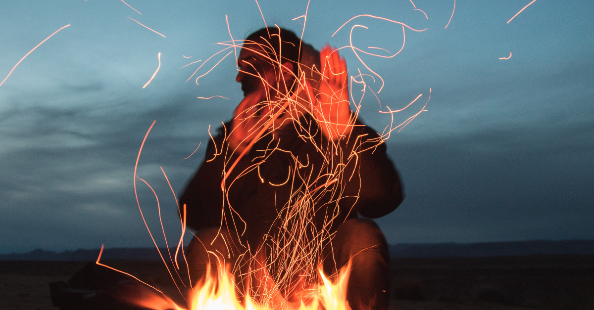 man sitting so close to flames in fire outdoors at night sparks flying hands up