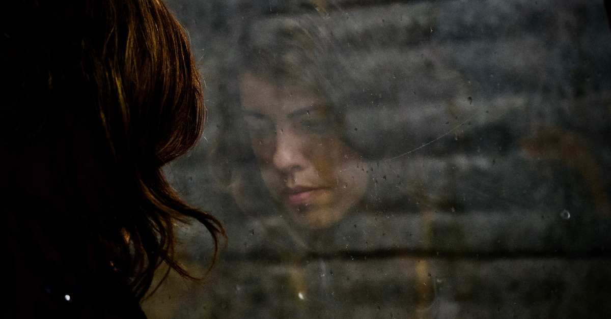 sad womans reflection looking out of window with raindrops, a prayer of faith when theres no fight left in you