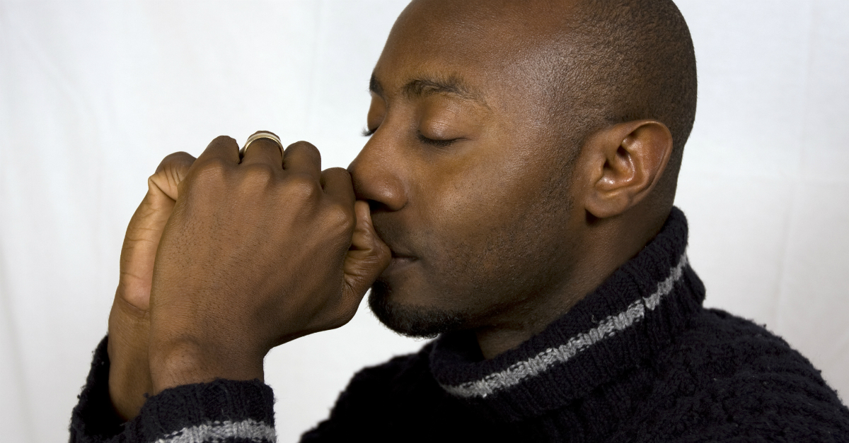 man praying peacefully eyes closed