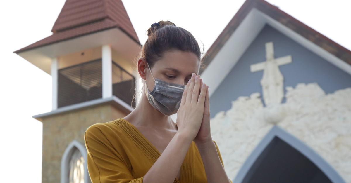 woman with coronavirus mask on praying outside church