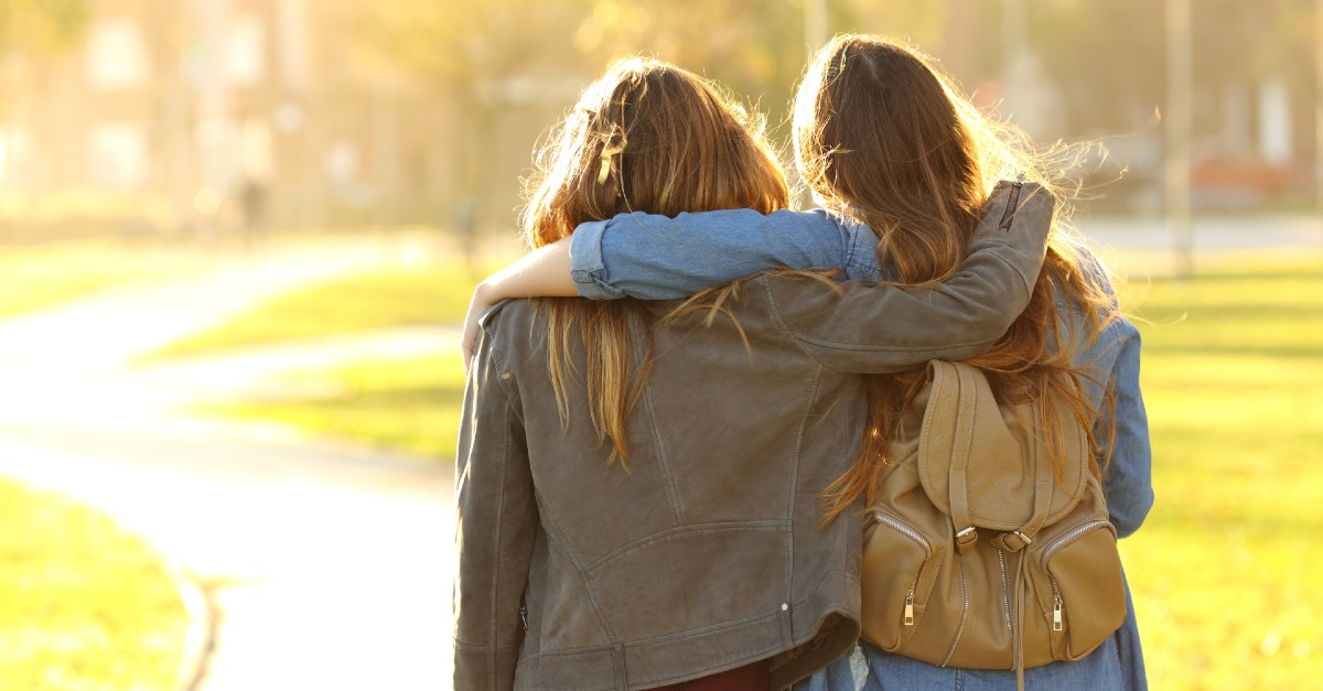 Two women, arms around each other, walk away from the camera on a campus in the morning light
