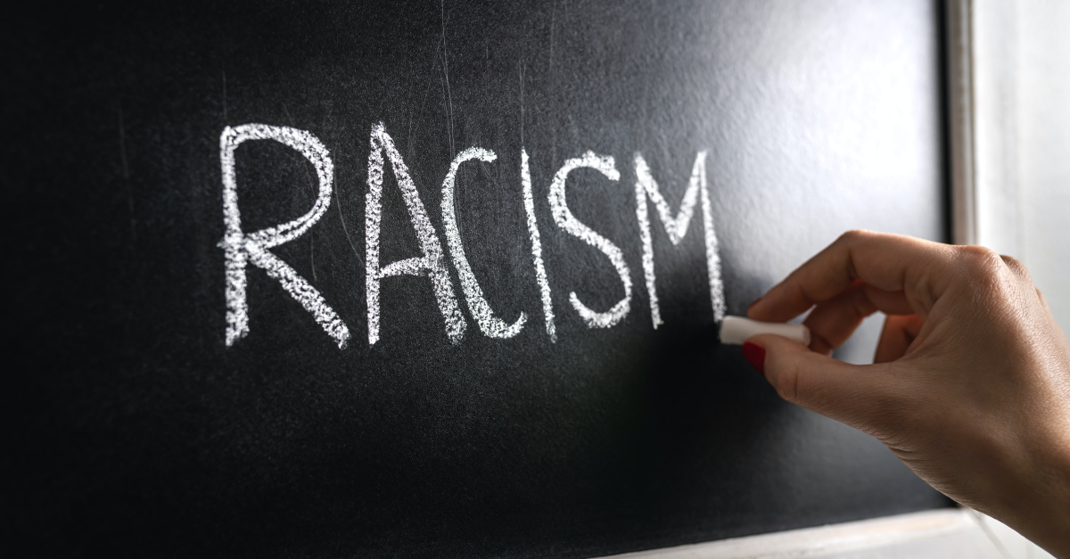 The word racism written on a blackboard, Praying for an end to racism for Pentecost