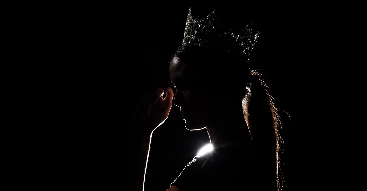 Queen silhouetted in black looking sad