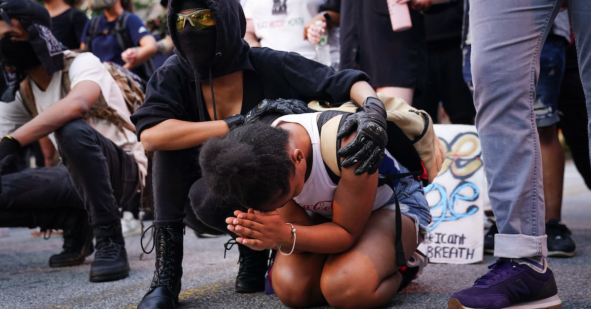Protestor praying at protest with friend holding her