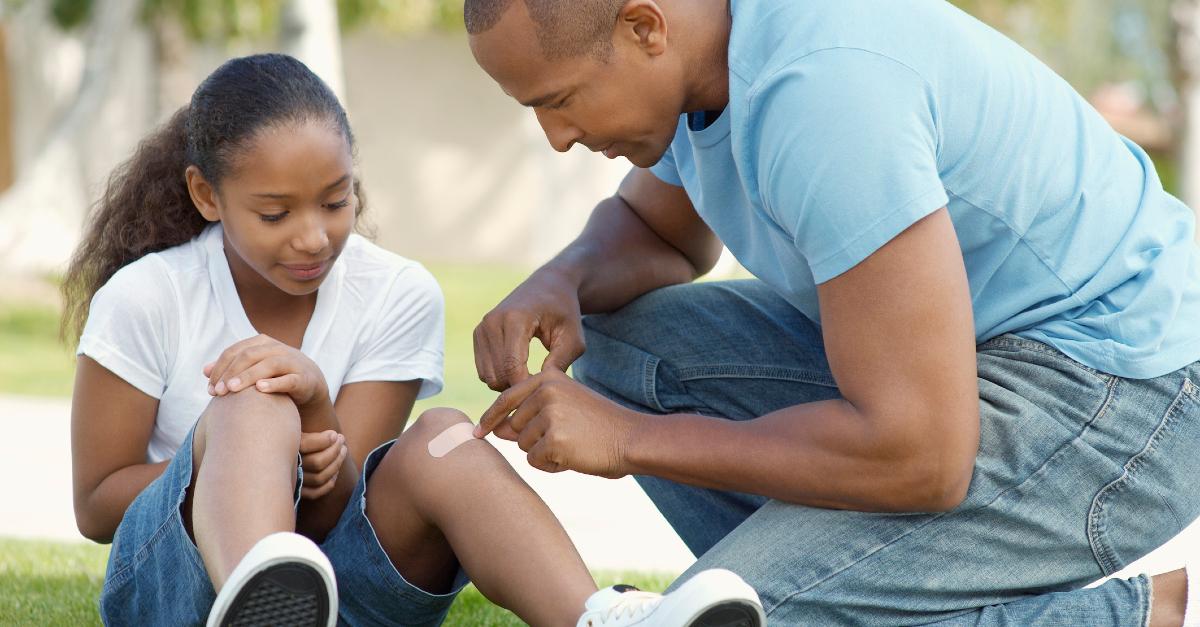 dad putting bandaid on daughter