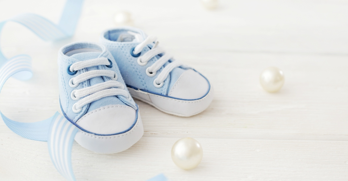 Blue baby shoes surrounded by ribbon pearls