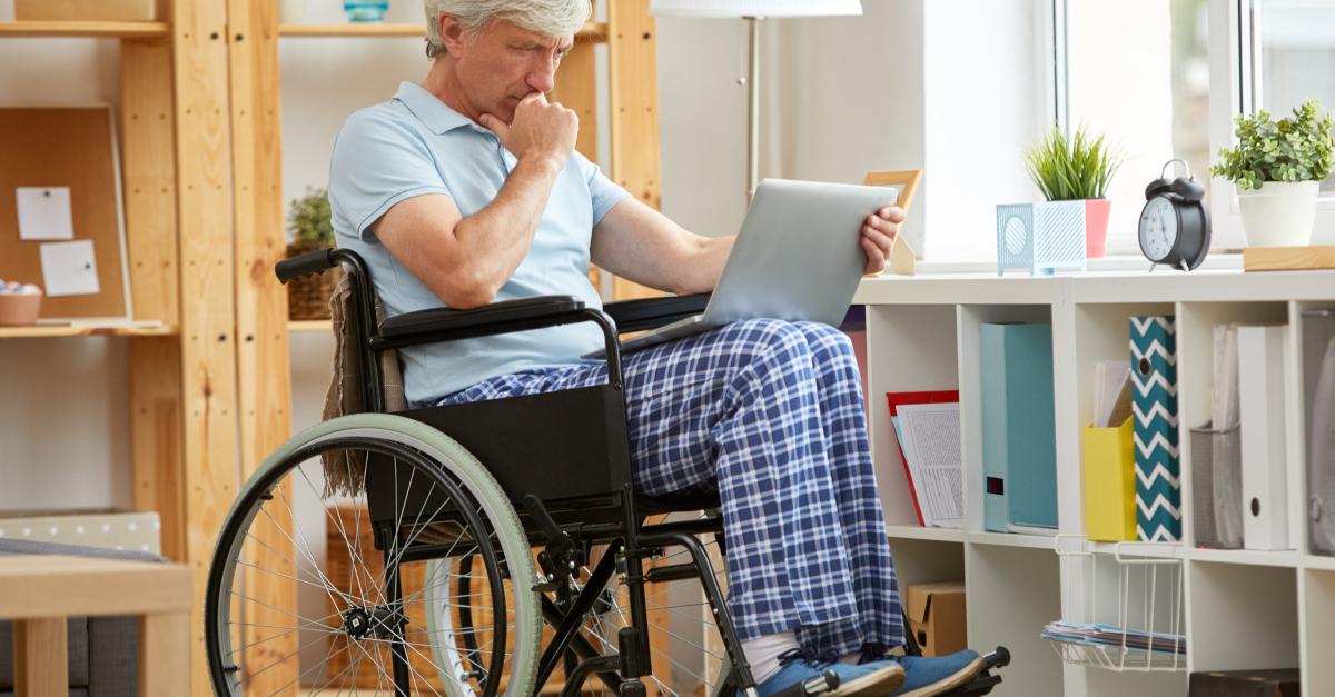 senior man in wheelchair watching church online on laptop