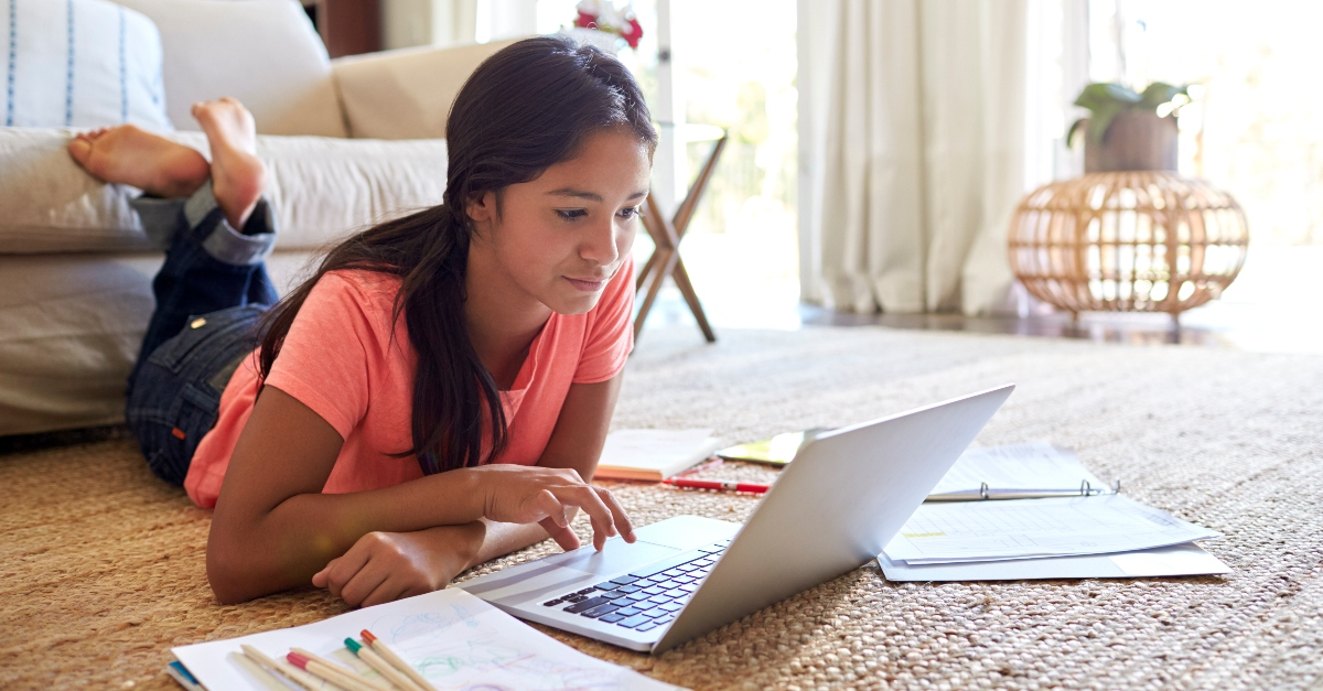 teenage girl working on homework and studying on living room floor, teach teens true definition of success