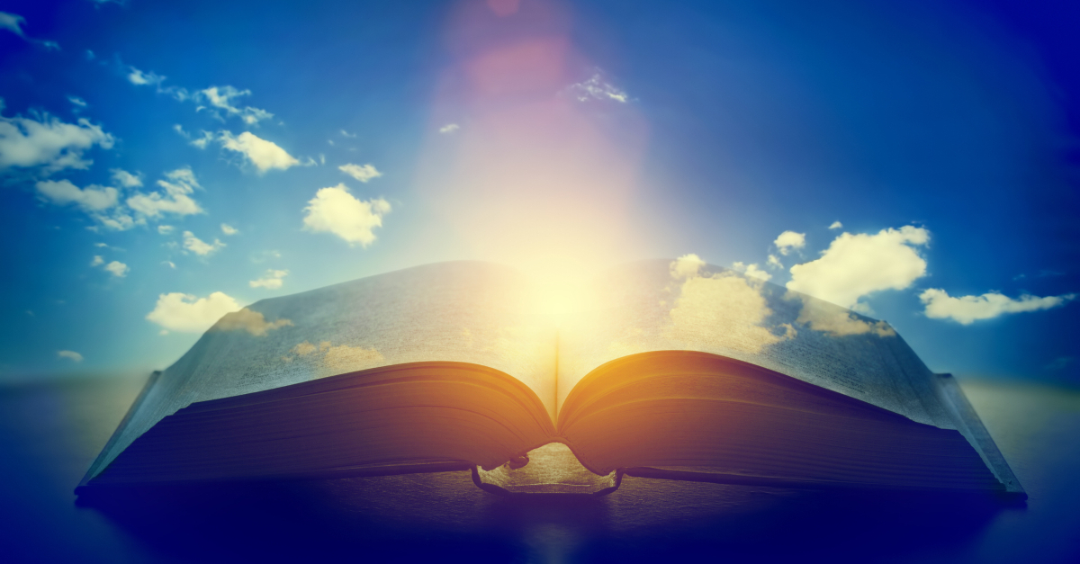 open bible with blue sky background and glow from center