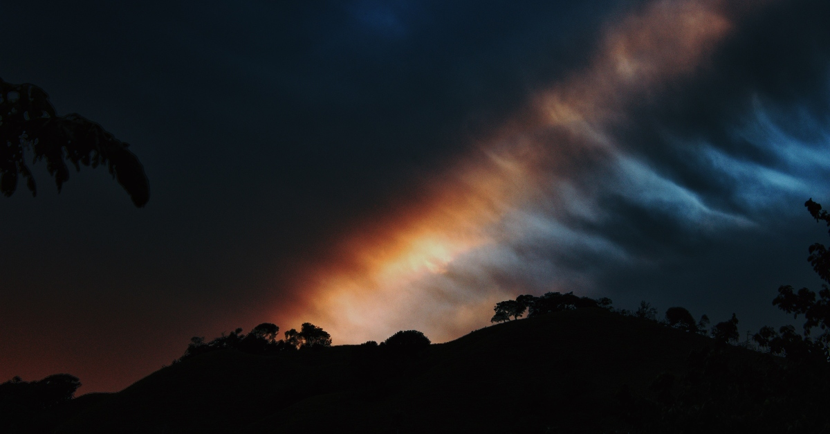 silhouette of hillside with dark clouds and rainbow, bible verses of hope