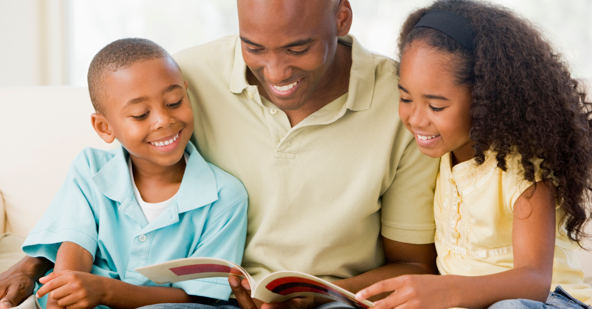 dad reading book with young son and daughter