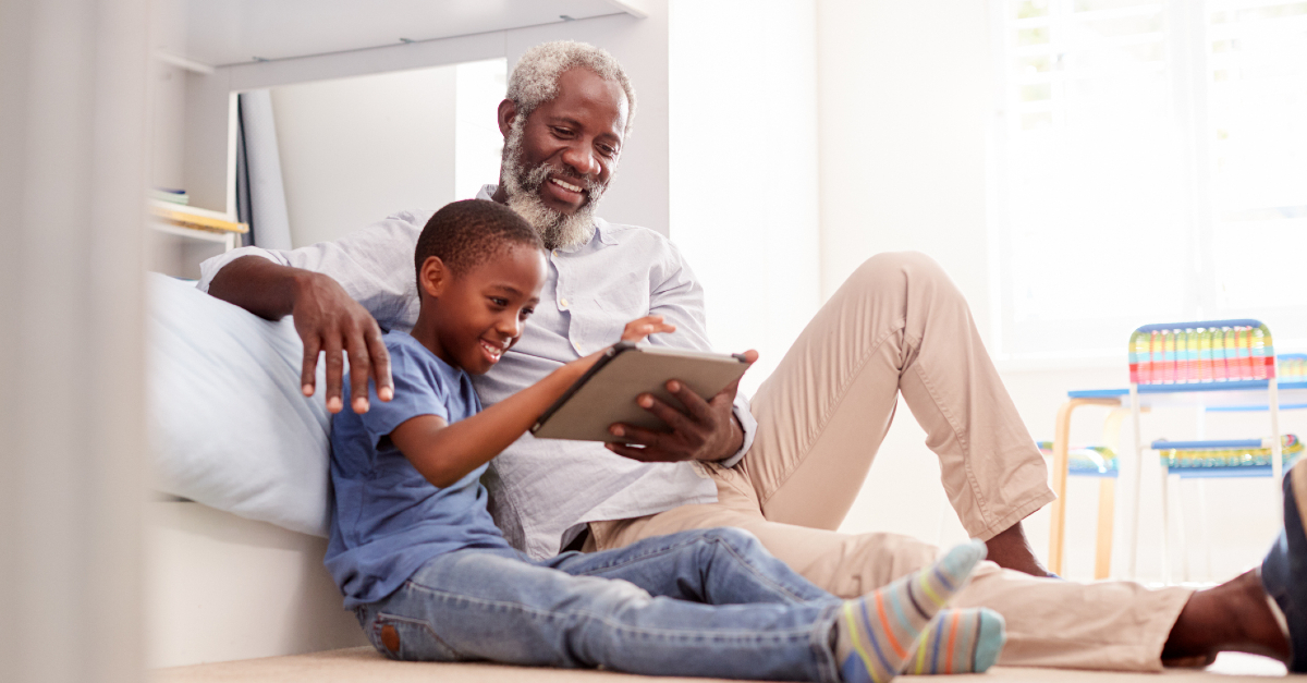 grandfather with kid looking at a tablet