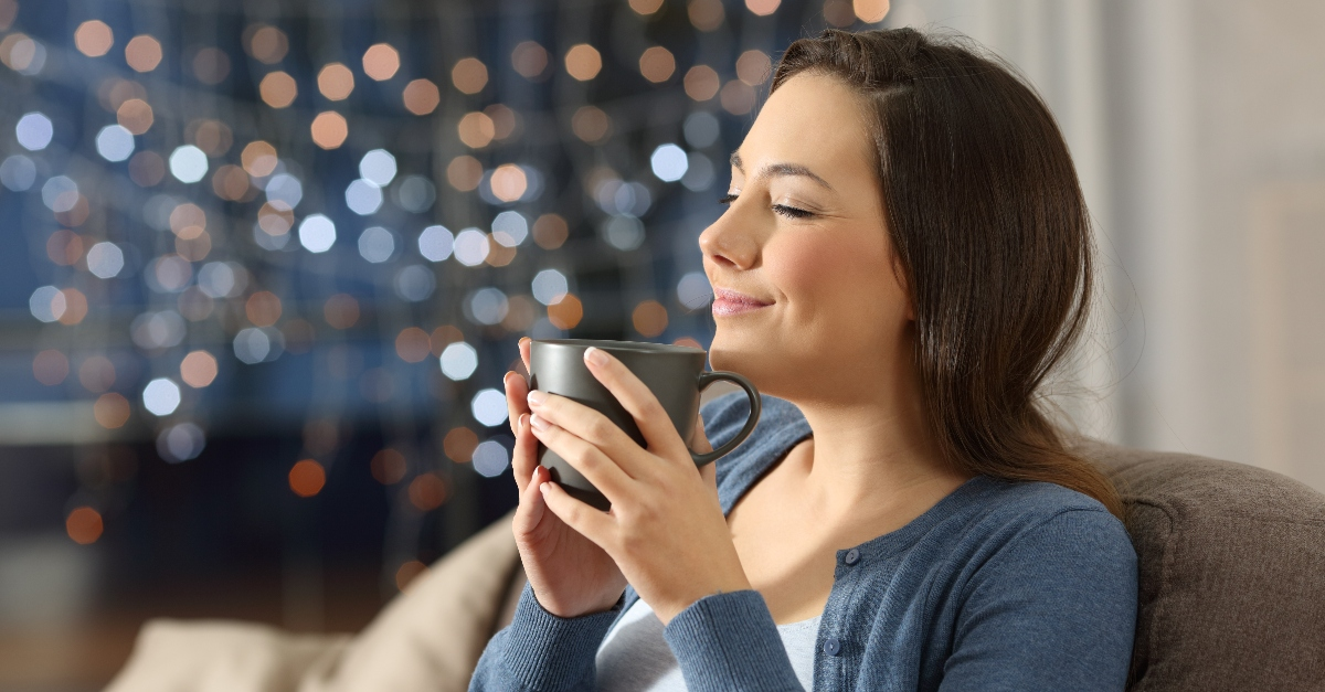 woman smiling sitting on couch with mug looking relaxed and peaceful