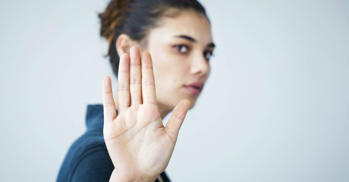 woman with hand up to camera rejecting