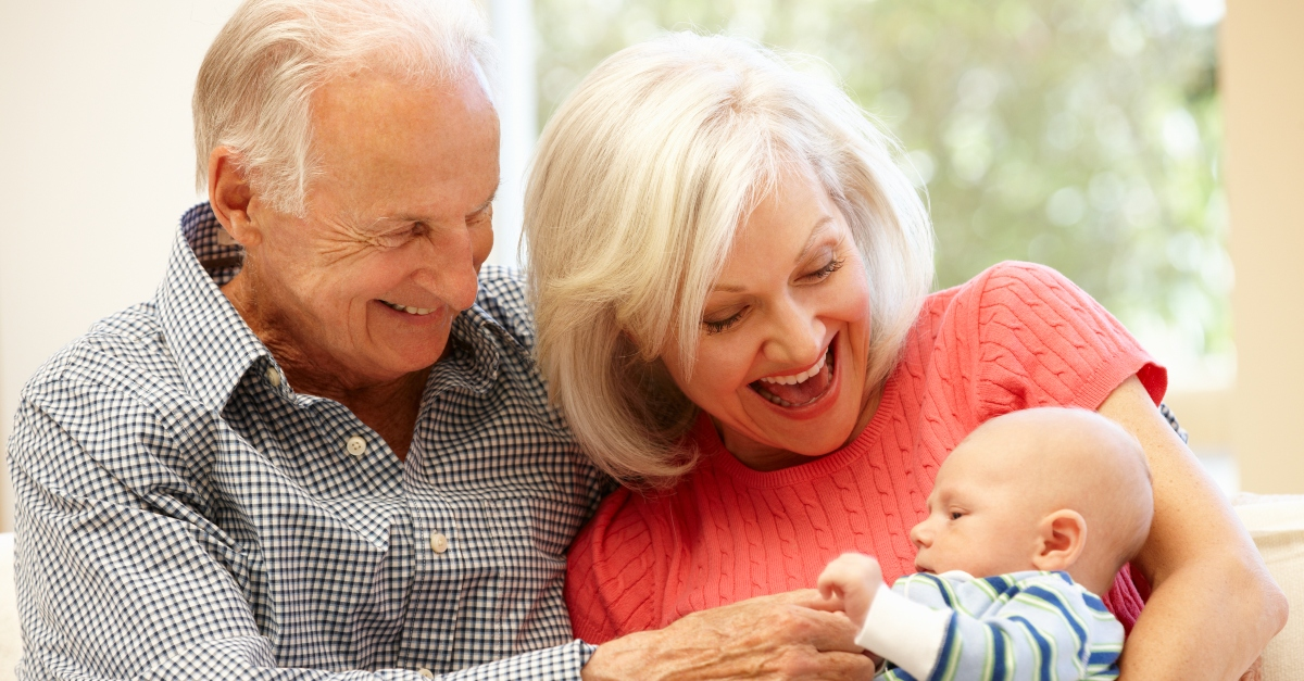 Older couple holding a baby boy