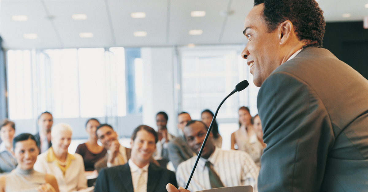 man speaking at podium with microphone to audience smiling