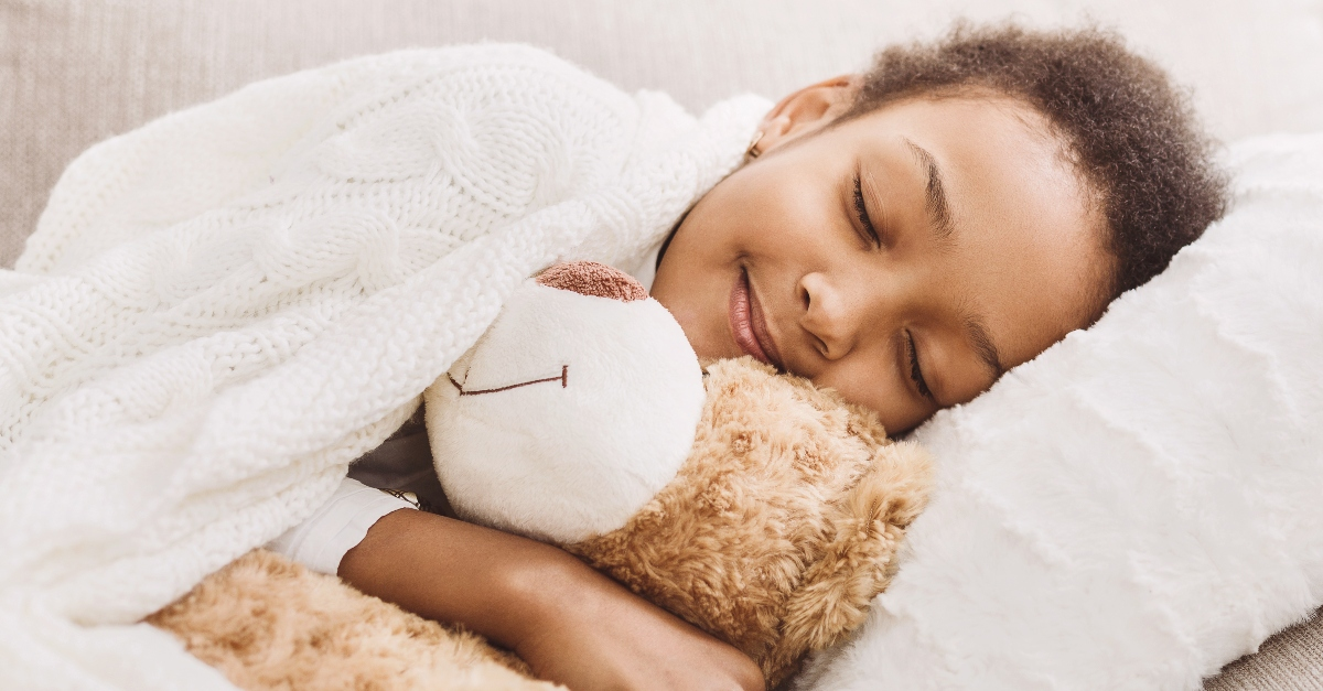 little girl sleeping peacefully in bed with smile on her face hugging a teddy bear, now I lay me down to sleep