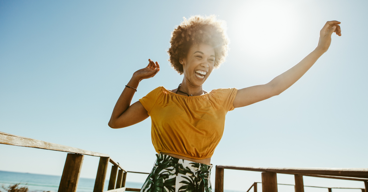 woman joyful arms raised at beach