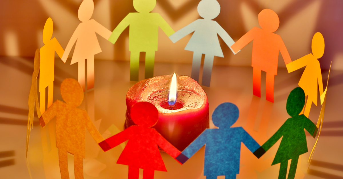 multicolored diversity of people paper cutouts encircling lit red candle