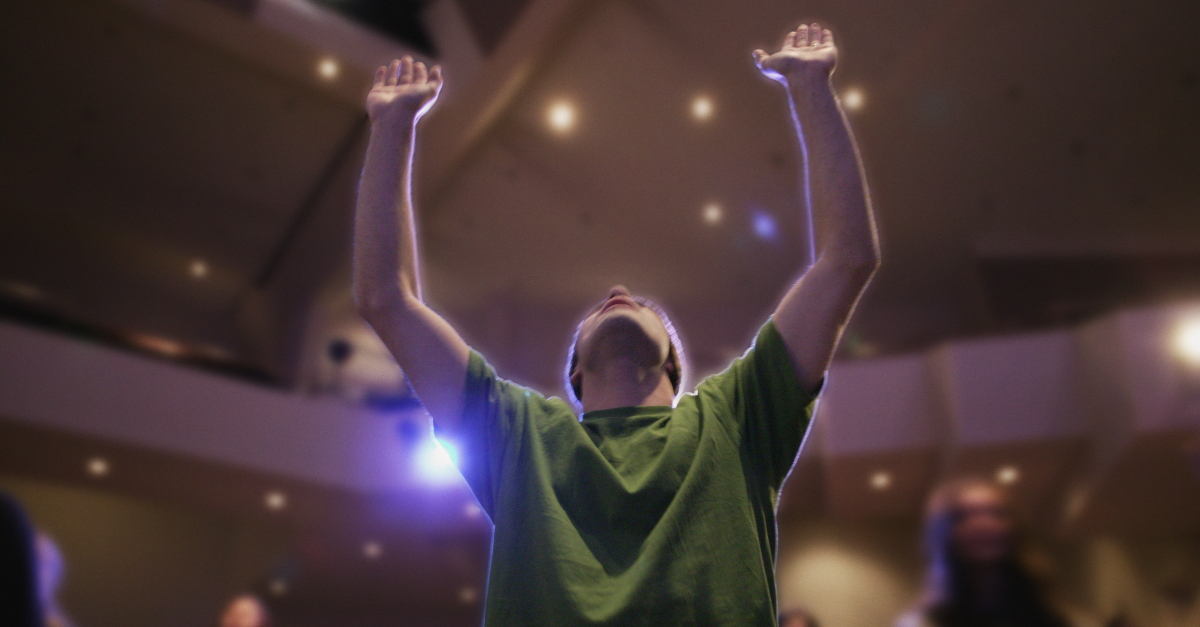 man in church arms up in prayer and praise