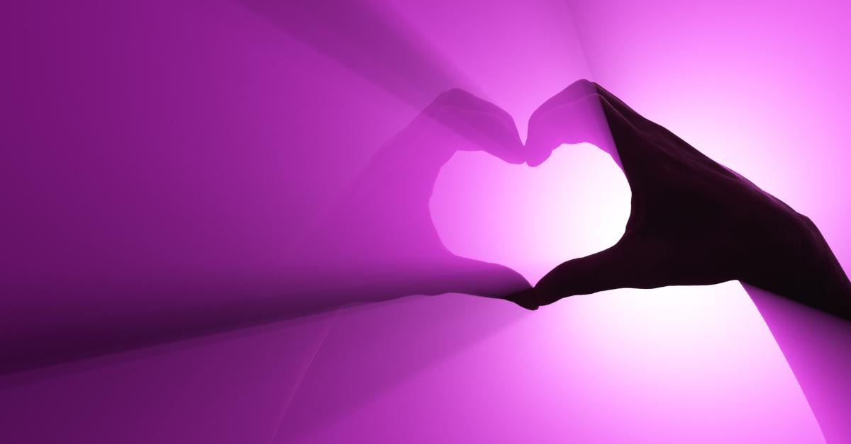 hands making heart shape with purple light shining through