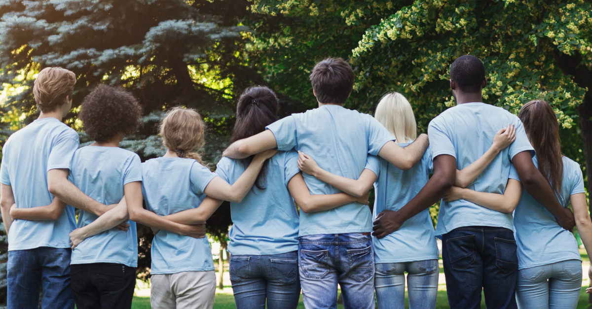 back view of diverse adult volunteers in group hug in a row