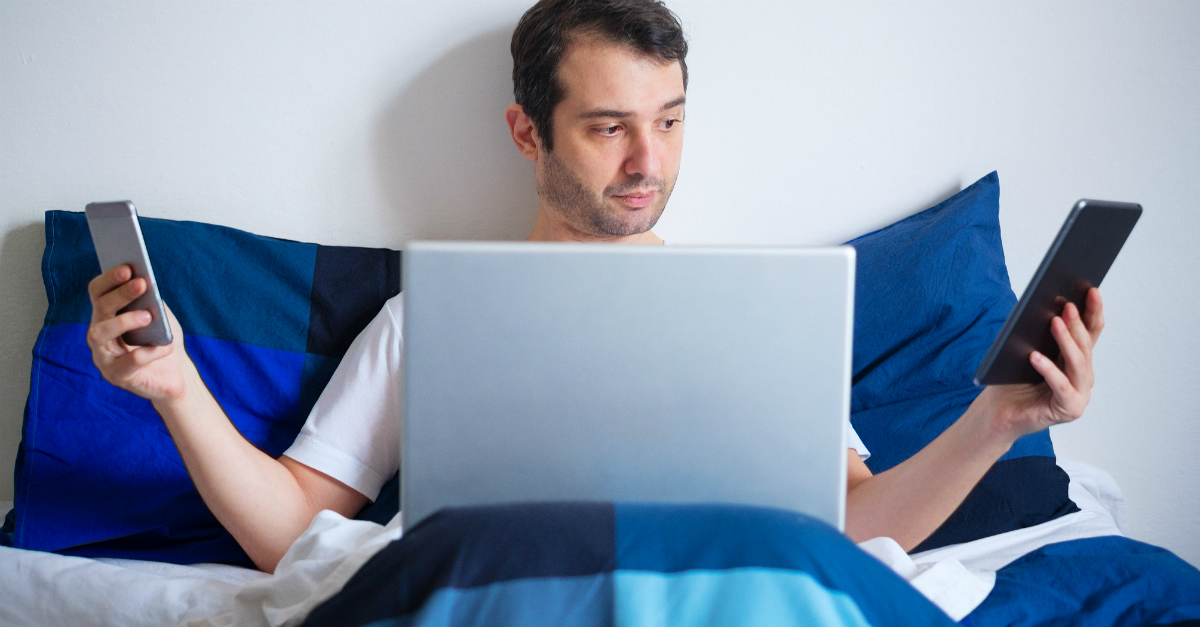 man tired in bed on two phones and laptop