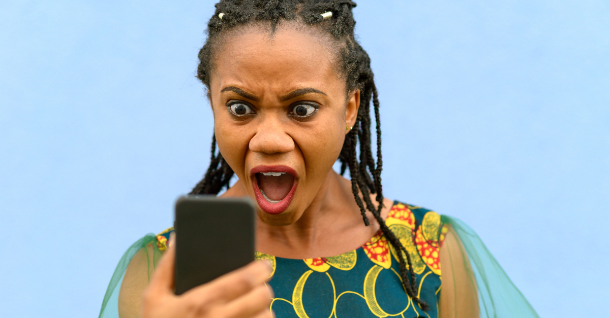 woman alarmed staring at cell phone in disbelief