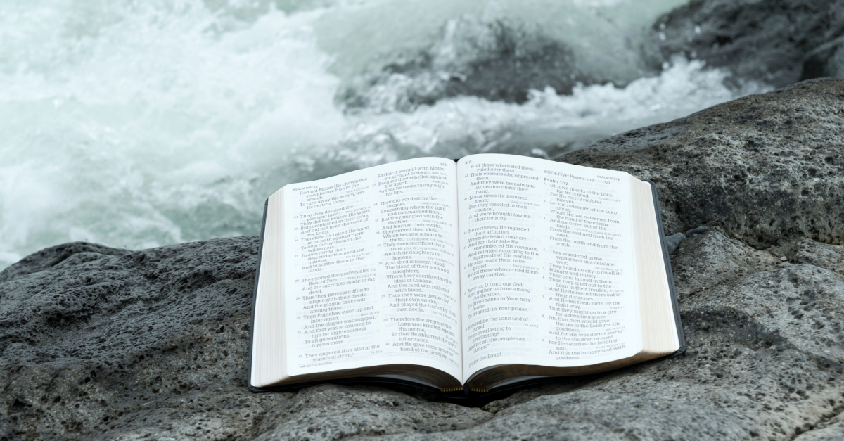 bible open on rock at sea to book of psalms for comfort