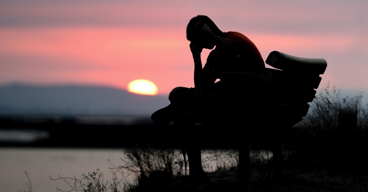young person sitting on a bench at sunset looking tired and discouraged, prayer for most painful memories