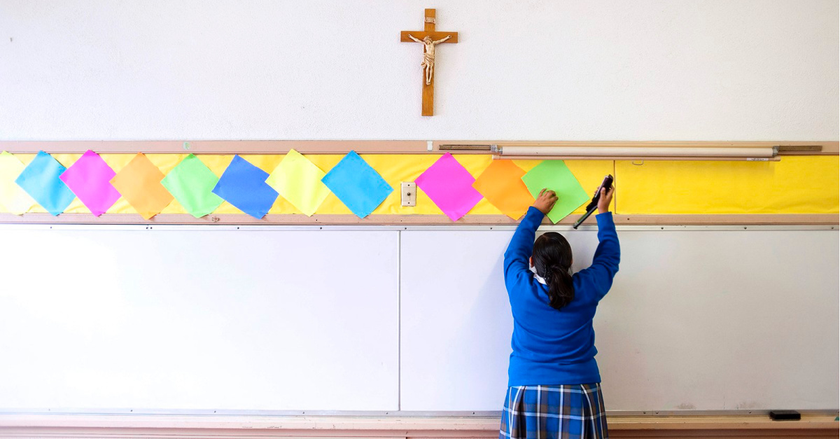 A Catholic school student hanging up fliers, Catholic schools in LA plan to reopen in the Fall