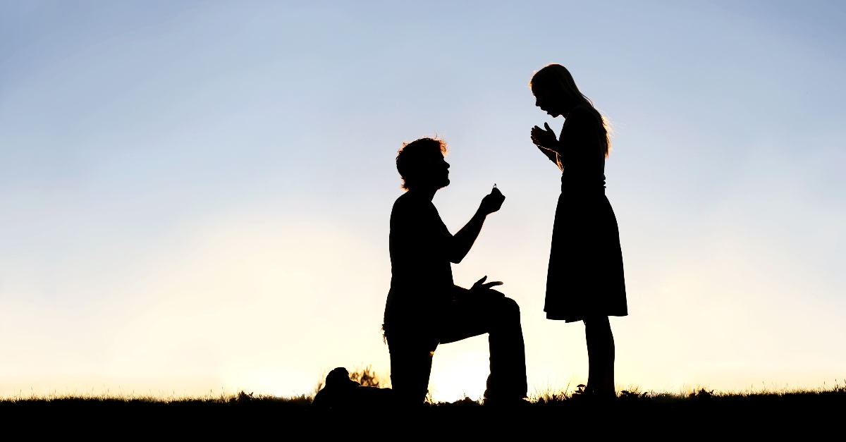 silhouette of man on knee asking woman to marry him, ready to marry