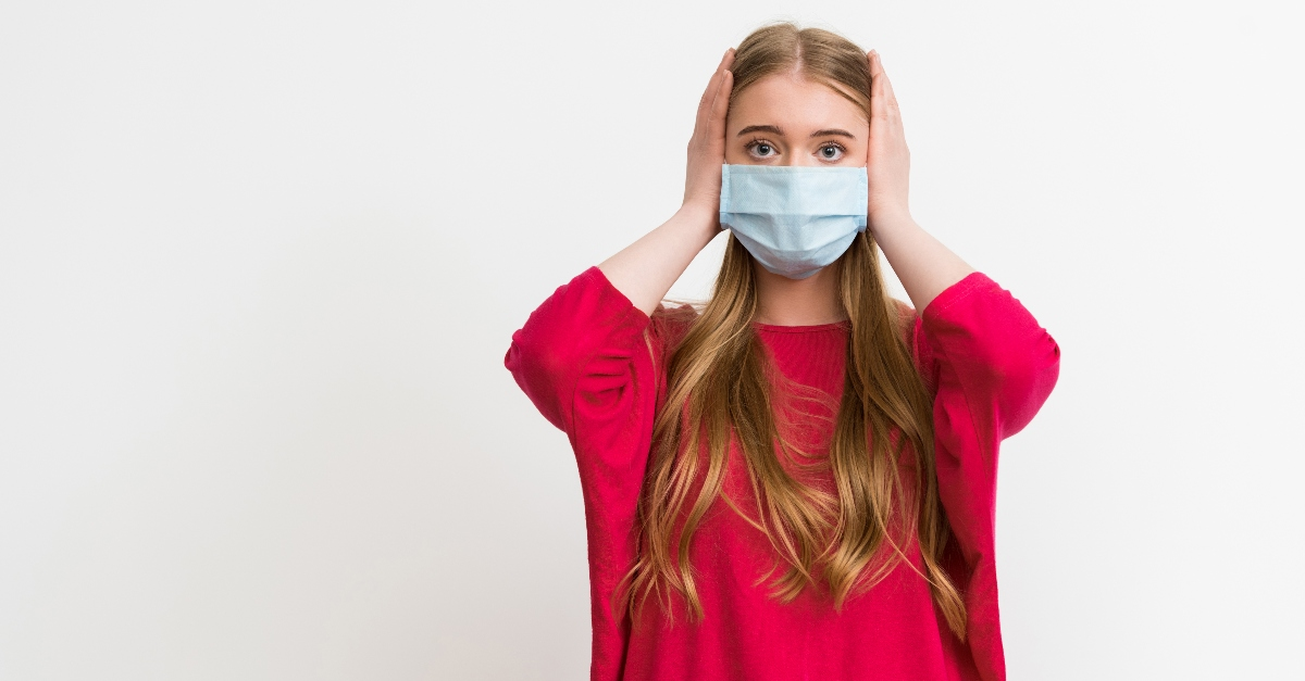young woman with hands over hears wearing a mask, not listening anymore