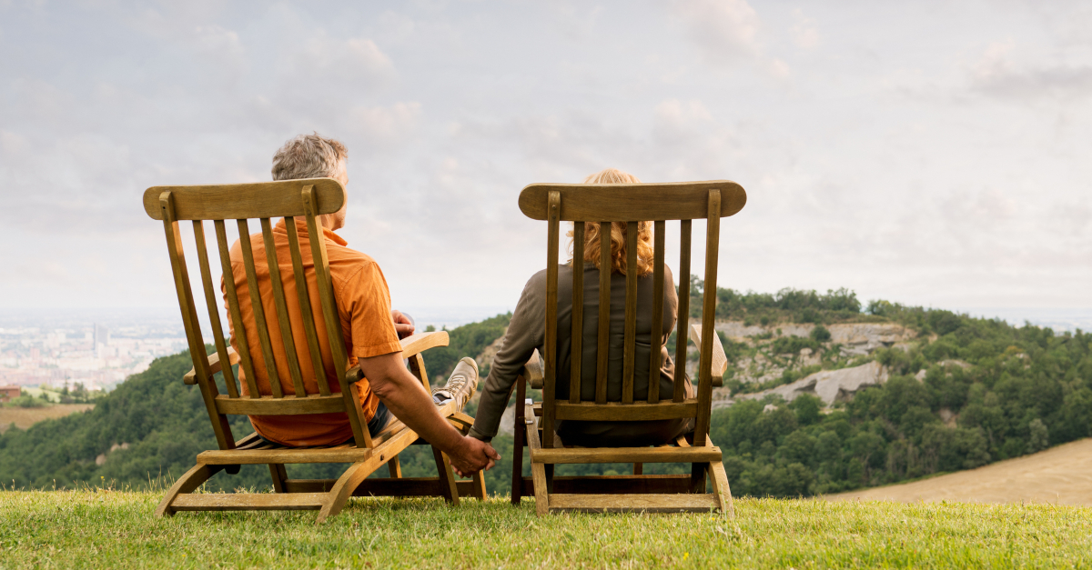 senior couple on scenic mountain overlook holding hands in deck chairs