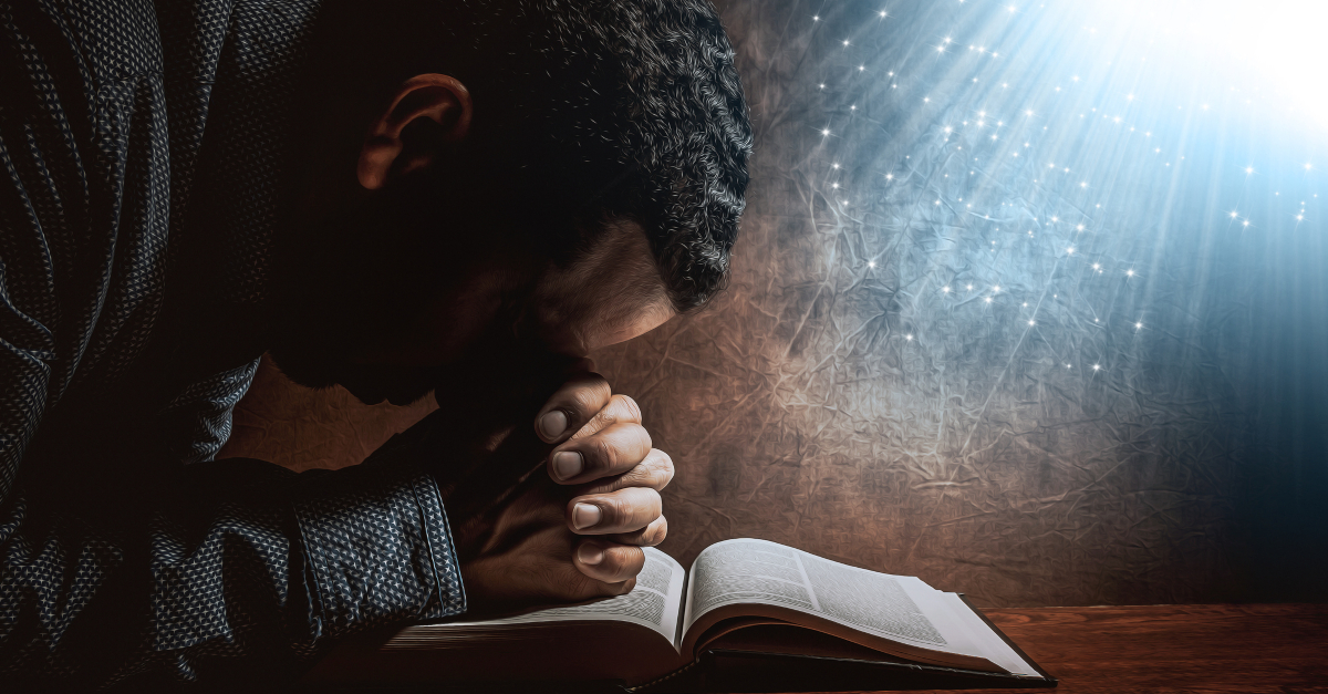 man resting head on praying hands on open bible light streaming above holy spirit