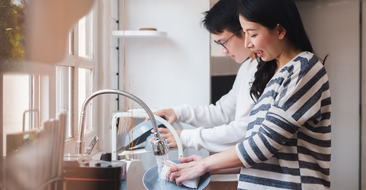 couple cleaning together in kitchen