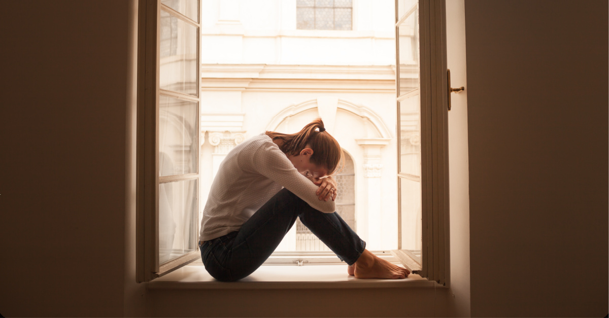 A stressed woman sitting on a window sill, Ed Young speaks on the virus of fear
