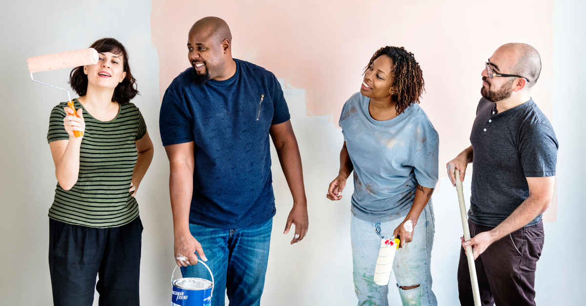 four adults painting wall together