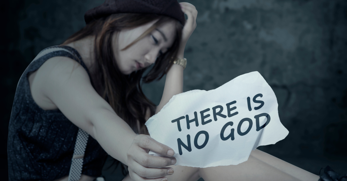 atheist girl holding paper sign there is no God