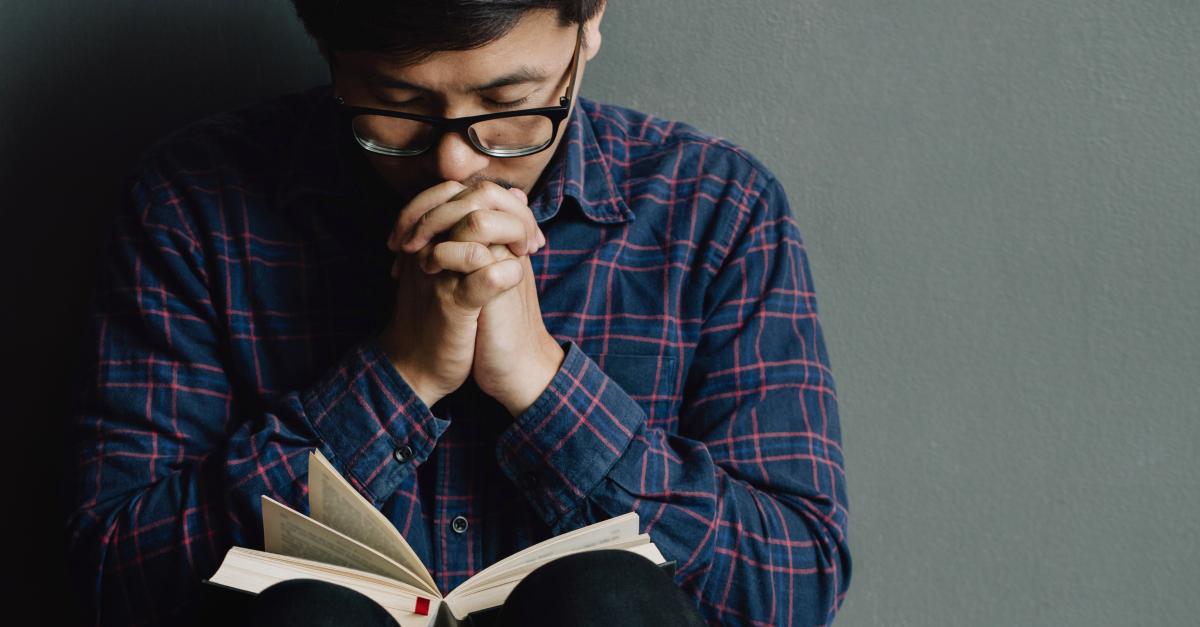 man eyes closed praying with Bible open on lap