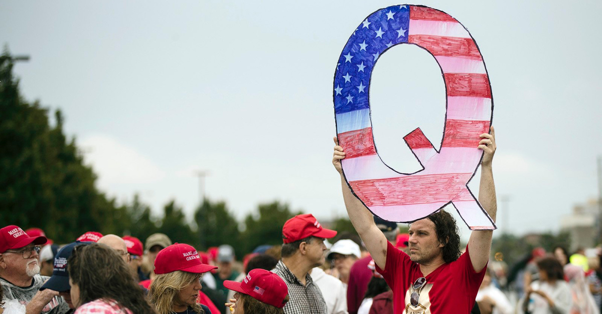 Man holding a giant Q sign, The struggle with QAnon coming to your church