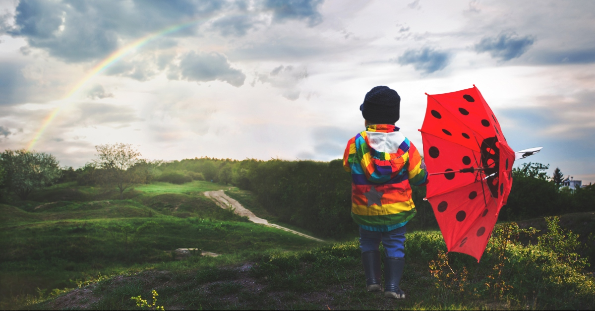 Kid with a rainbow coat looking at a rainbow in the sky