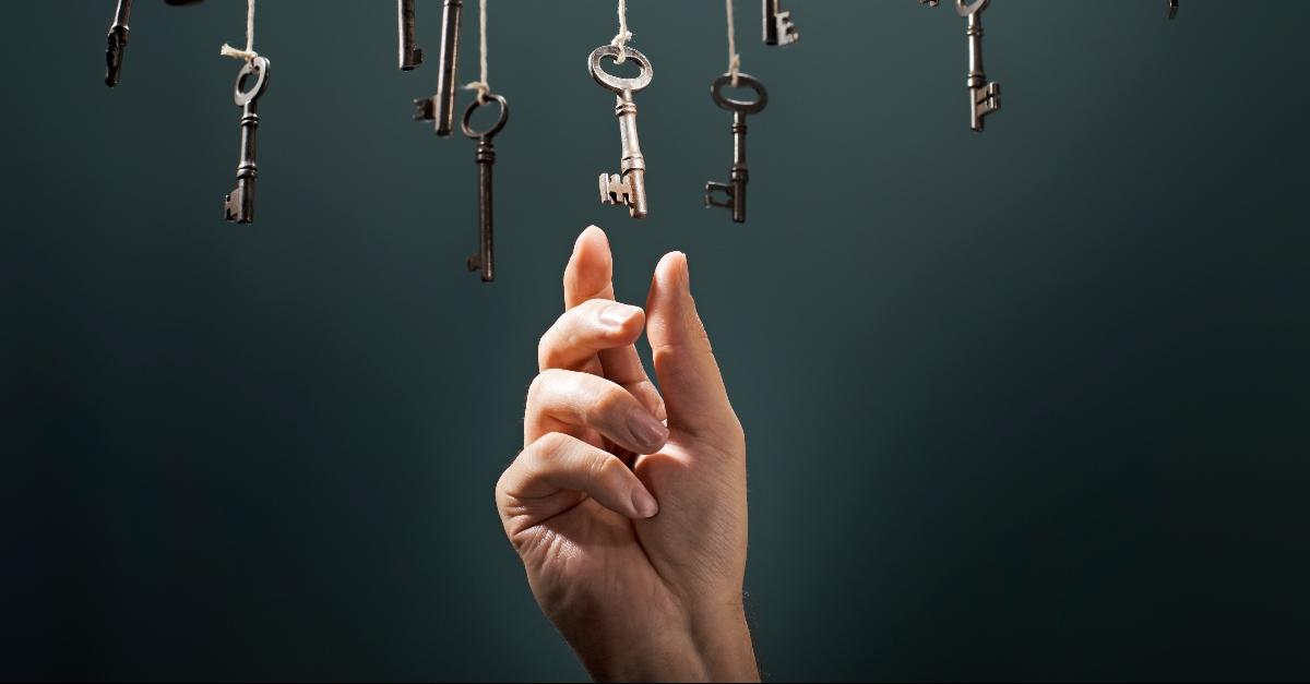 A hand reaching for a key amongst many keys