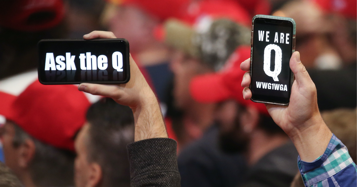 QAnon signs on phones, QAnon started with a post on a messaging board