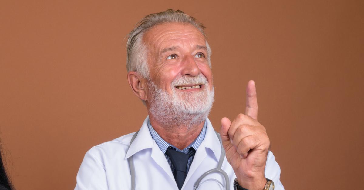 Hombre senior en bata de médico y un estetoscopio apuntando hacia Dios sonriendo