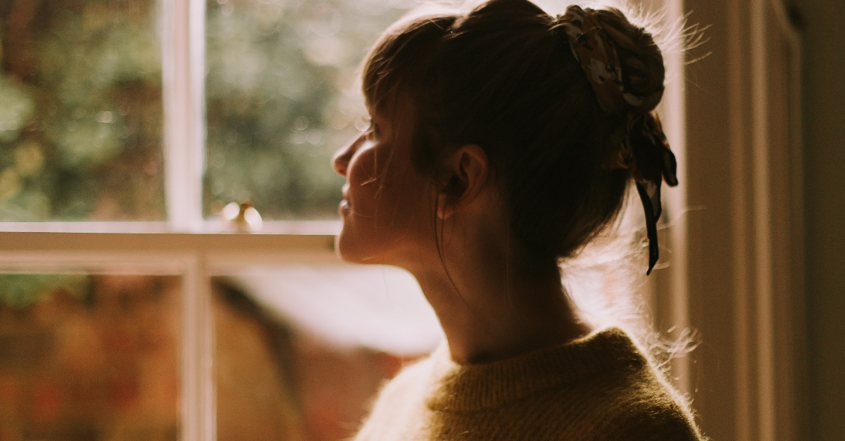 woman in sweater looking out window, prayer for new purpose new day