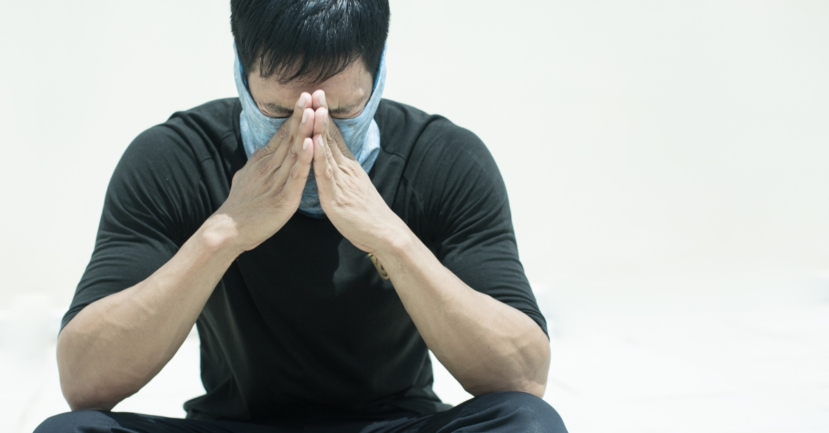 man praying for healing from coronavirus with face mask on