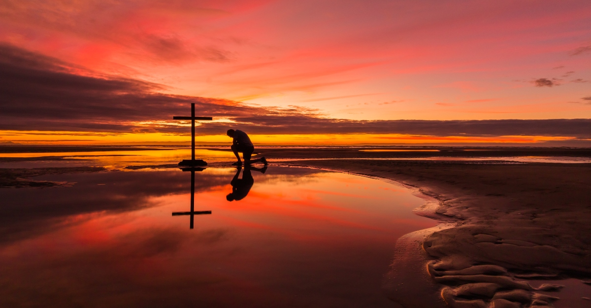 man kneeling before cross on beautiful beach sunset, every knee shall bow meaning